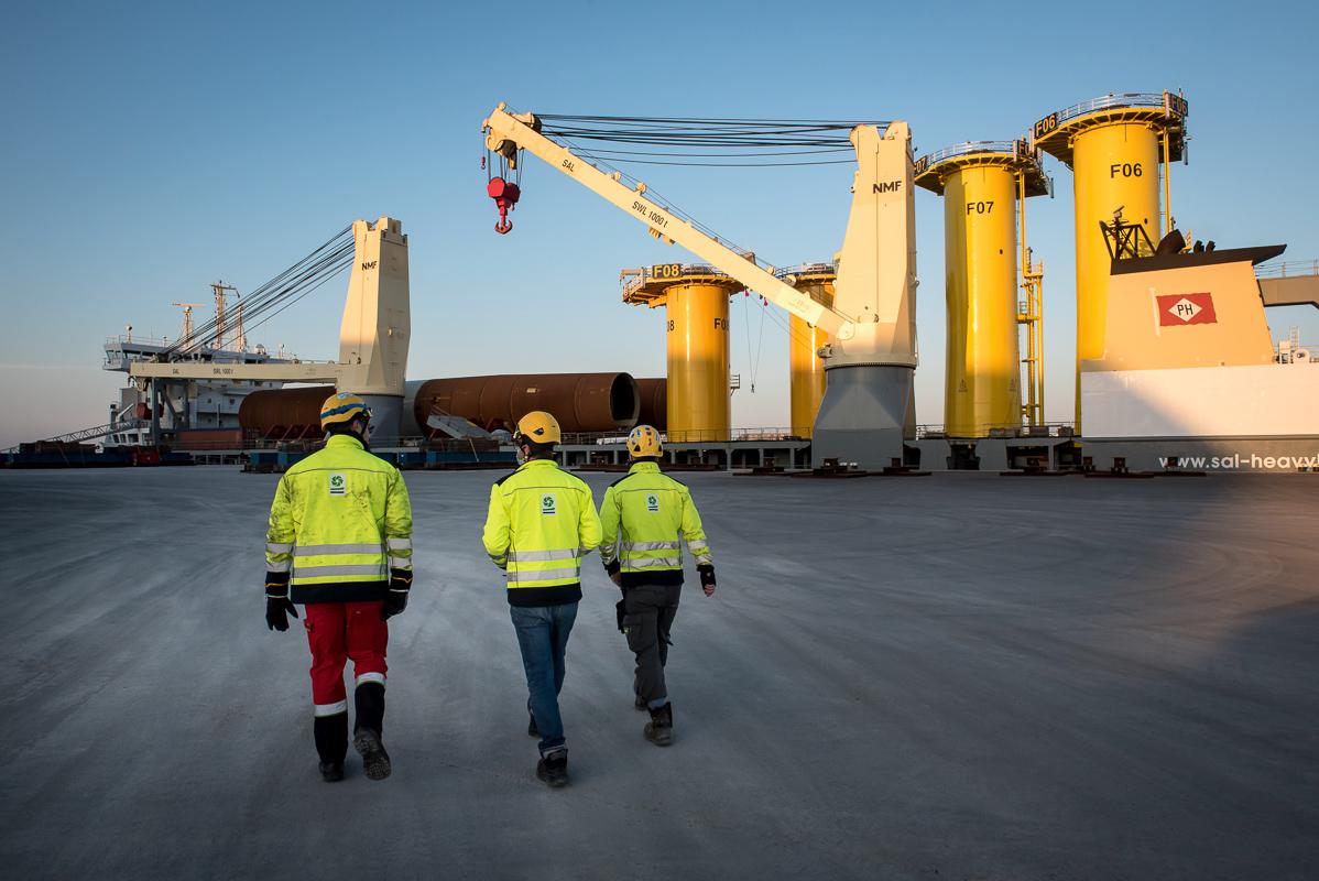 3 ouvriers se dirigent vers le quai ou est amarré le navire avec les fondations des éoliens, port maritime de la Rochelle