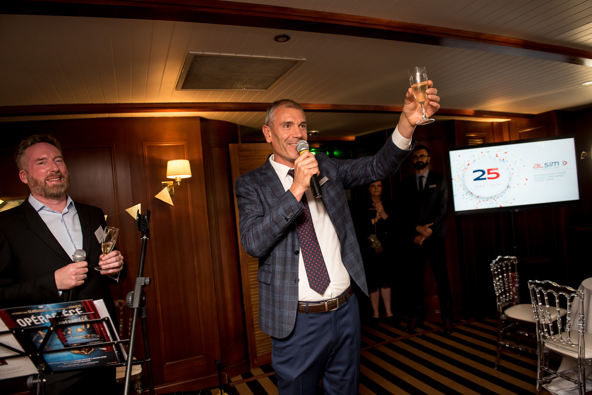 Jean-Paul Monnin, head of ALSIM, raises a glass during 25th company anniversary celebrations on boat on Seine in Paris