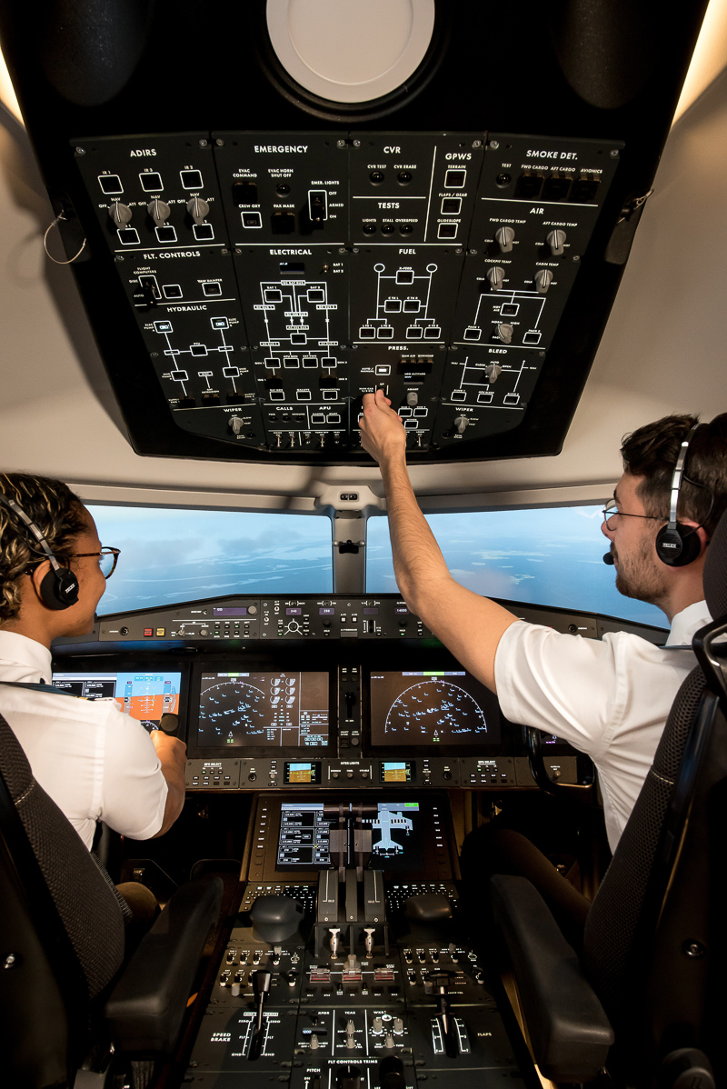 Interior view cockpit, Alsim Airliner flight simulator, two pilots, man and woman using the controls