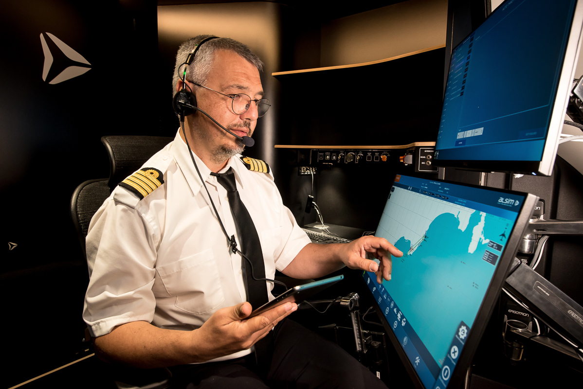 Flight instructor interacts with computer screen in Alsim Airliner flight simulator