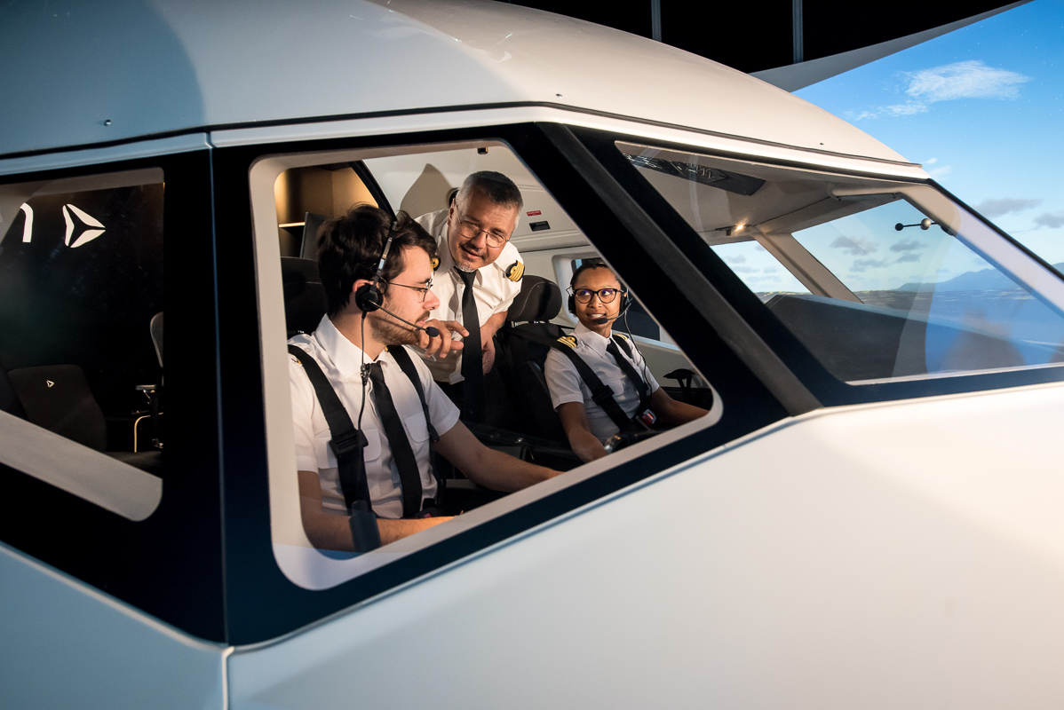 External view of Alsim Airliner flight simulator, with instructor guiding man and woman trainee pilots