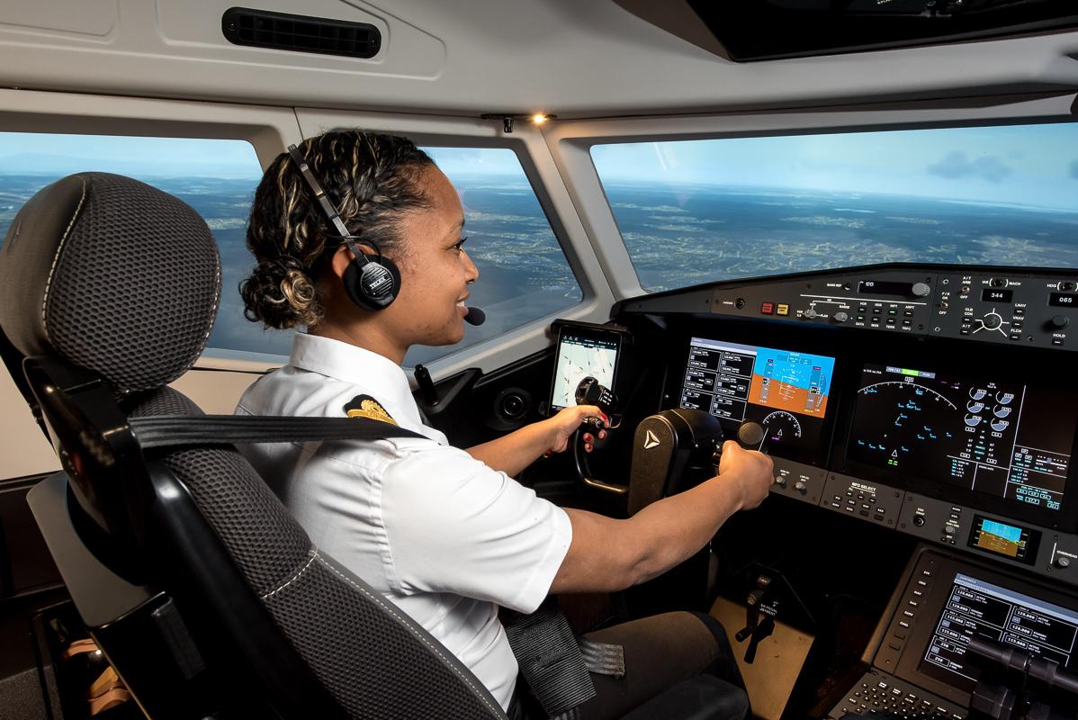 Woman in pilot seat flies Alsim's Airliner flight simulator