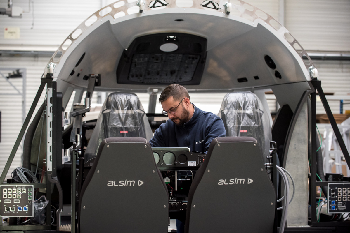 Technician working on Alsim flight simulator on production line